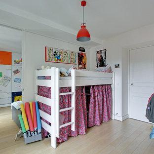Inspiration pour une chambre d'enfant de 4 à 10 ans design de taille moyenne avec un mur blanc et un sol en bois clair.