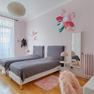 Aménagement d'une chambre d'enfant de 4 à 10 ans scandinave avec un mur rose et un sol en bois brun.