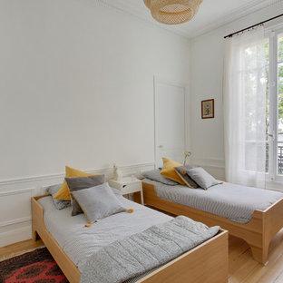 Cette photo montre une chambre d'enfant de 4 à 10 ans chic de taille moyenne avec un mur jaune, un sol en bois clair et un sol beige.