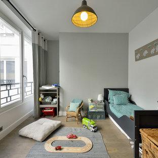 Cette photo montre une chambre d'enfant de 4 à 10 ans chic de taille moyenne avec un mur gris et un sol en bois brun.