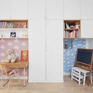 Exemple d'une chambre neutre de 1 à 3 ans tendance avec un bureau, un mur multicolore et un sol en bois clair.