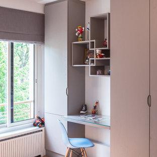 Idée de décoration pour une chambre de garçon de 4 à 10 ans design de taille moyenne avec un bureau, un mur blanc et un sol en bois brun.