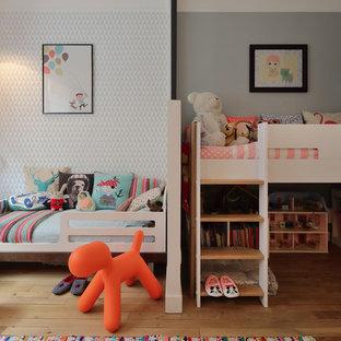 Réalisation d'une chambre d'enfant de 4 à 10 ans design de taille moyenne avec un mur gris et un sol en bois clair.