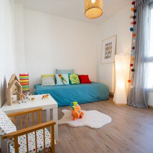 Exemple d'une petit chambre d'enfant de 1 à 3 ans scandinave avec un mur blanc, un sol en bois brun et un sol marron.