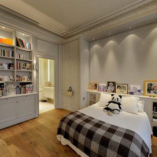 Cette image montre une grand chambre d'enfant design avec un mur beige et un sol en bois brun.