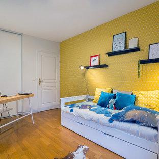 Réalisation d'une chambre d'enfant design avec un mur jaune, un sol en bois brun et un sol marron.