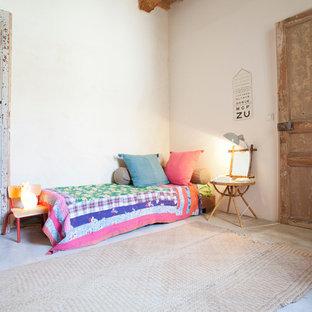 Aménagement d'une grand chambre d'enfant de 4 à 10 ans éclectique avec un mur blanc et béton au sol.
