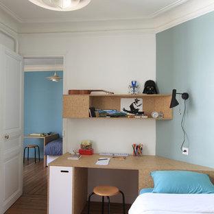 Cette image montre une chambre neutre de 4 à 10 ans design de taille moyenne avec un bureau, un sol en bois brun et un mur multicolore.