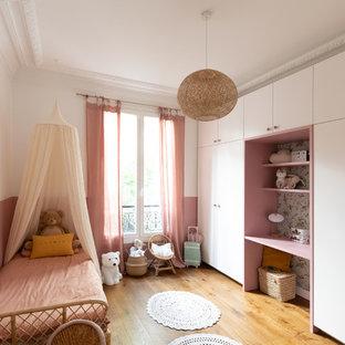 Esempio di una cameretta per bambini da 4 a 10 anni design di medie dimensioni con pareti rosa, parquet scuro e pavimento marrone
