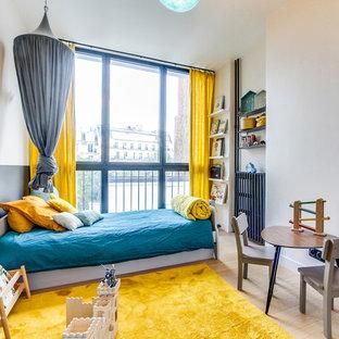Aménagement d'une chambre d'enfant contemporaine avec un mur blanc, un sol en bois clair et un sol beige.
