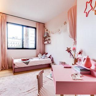 Exemple d'une chambre d'enfant tendance avec un mur blanc, un sol en bois clair et un sol beige.