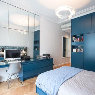 Exemple d'une grand chambre d'enfant tendance avec un bureau, un mur blanc et un sol en bois brun.