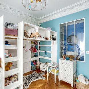 Cette photo montre une chambre d'enfant de 4 à 10 ans éclectique avec un mur bleu et un sol en bois brun.