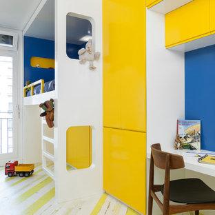 Cette image montre une chambre de garçon de 4 à 10 ans design de taille moyenne avec un bureau, un mur bleu, un sol en bois peint et un sol multicolore.
