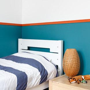 Exemple d'une chambre d'enfant de 1 à 3 ans tendance avec un mur multicolore et un sol en bois brun.