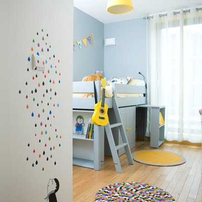 Example of a mid-sized trendy gender-neutral light wood floor kids' room design in Paris with blue walls