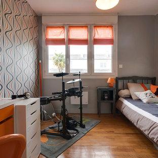 Immagine di una piccola cameretta per bambini minimal con pareti grigie e pavimento in legno massello medio