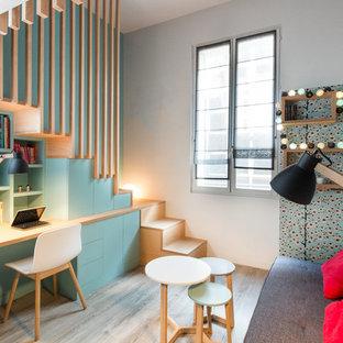 Cette photo montre une petit chambre d'enfant tendance avec un bureau, un mur gris, un sol en bois clair et un sol beige.