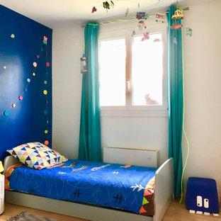 Inspiration pour une petit chambre d'enfant de 4 à 10 ans design avec un mur bleu, un sol en bois brun et un sol marron.