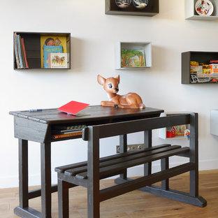 Cette photo montre une chambre neutre de 4 à 10 ans scandinave de taille moyenne avec un bureau, un mur blanc et un sol en bois brun.