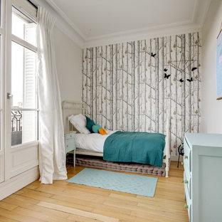 Cette image montre une chambre d'enfant de 4 à 10 ans nordique de taille moyenne avec un mur beige, un sol en bois clair et un sol beige.
