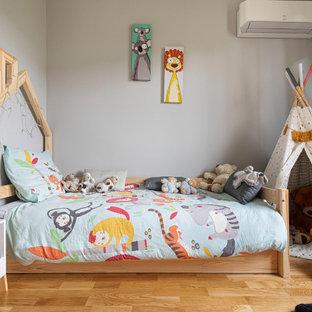 Idées déco pour une petit chambre d'enfant contemporaine avec un mur gris et un sol en bois clair.