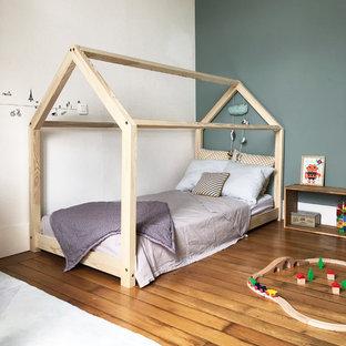Inspiration pour une chambre neutre nordique avec un mur gris, un sol en bois brun et un sol marron.