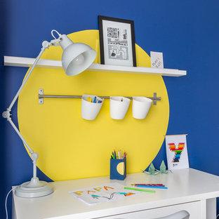 Idée de décoration pour une chambre de garçon de 4 à 10 ans design de taille moyenne avec un bureau, un mur bleu et un sol en bois clair.