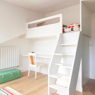 Idée de décoration pour une chambre neutre de 4 à 10 ans design de taille moyenne avec un bureau, un mur blanc et un sol en bois clair.