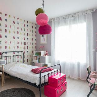 Idée de décoration pour une chambre d'enfant de 4 à 10 ans design de taille moyenne avec un sol en bois clair et un mur multicolore.