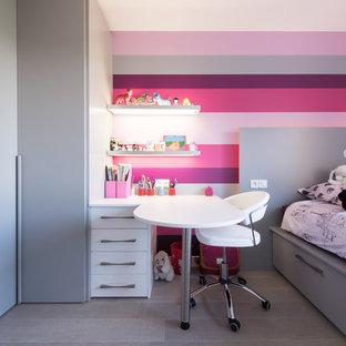 Cette image montre une chambre de fille de 4 à 10 ans design de taille moyenne avec un mur multicolore, un bureau et un sol en bois clair.