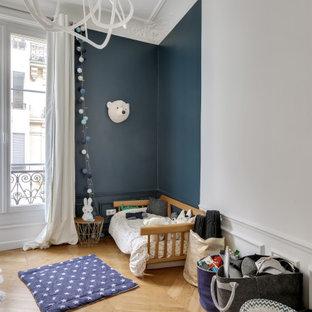 Réalisation d'une chambre d'enfant de 1 à 3 ans design de taille moyenne avec un mur bleu, un sol en bois clair et un sol beige.