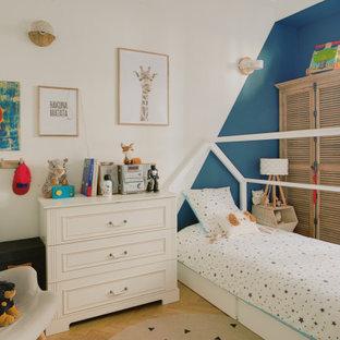 Inspiration pour une chambre d'enfant de 1 à 3 ans design de taille moyenne avec un mur bleu, un sol en bois clair et un sol beige.