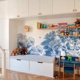 Cette image montre une chambre d'enfant de 1 à 3 ans design de taille moyenne avec un mur bleu, un sol en bois clair et un sol beige.