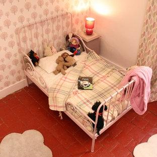 Immagine di una cameretta per bambini da 4 a 10 anni minimal di medie dimensioni con pareti rosa e pavimento in terracotta
