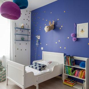 Exemple d'une chambre d'enfant de 1 à 3 ans tendance de taille moyenne avec un sol en bois clair et un mur multicolore.