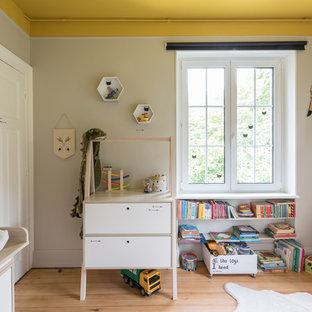 Modelo de dormitorio infantil de 1 a 3 años, minimalista, de tamaño medio, con paredes grises, suelo de madera clara y suelo beige