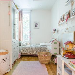 Exemple d'une chambre d'enfant chic avec un mur blanc, un sol en bois brun et un sol marron.