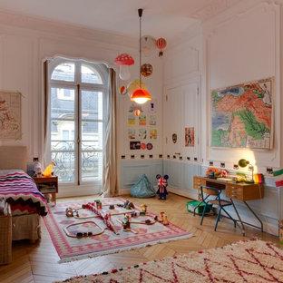Aménagement d'une chambre d'enfant de 1 à 3 ans contemporaine avec un mur blanc, un sol en bois brun et un sol marron.