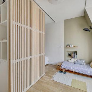Aménagement d'une chambre d'enfant contemporaine avec un mur vert, un sol en bois clair et un sol beige.