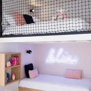 Aménagement d'une petit chambre d'enfant contemporaine avec un sol en bois clair et un mur rose.
