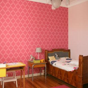 Idée de décoration pour une chambre d'enfant de 4 à 10 ans tradition de taille moyenne avec un mur rose et un sol en bois brun.