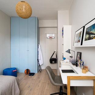 Inspiration pour une chambre d'enfant design avec un mur blanc, un sol en bois clair et un sol beige.