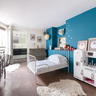 Cette image montre une grande chambre d'enfant de 4 à 10 ans bohème avec un sol en bois brun et un mur multicolore.