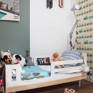 Réalisation d'une chambre d'enfant de 1 à 3 ans design de taille moyenne avec un sol en bois foncé et un mur gris.