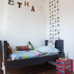 Idées déco pour une grand chambre d'enfant de 1 à 3 ans contemporaine avec un mur blanc et un sol en bois brun.