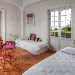 Idée de décoration pour une chambre d'enfant de 4 à 10 ans bohème avec un mur blanc et un sol en bois brun.