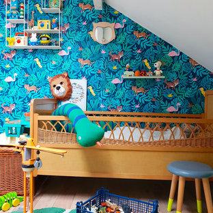 Cette image montre une chambre d'enfant de 1 à 3 ans bohème avec un mur multicolore, un sol en bois clair et un sol beige.