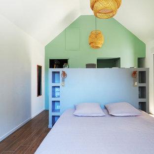Idée de décoration pour une chambre d'enfant marine avec un mur blanc, un sol en bois brun et un sol marron.