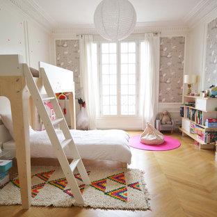 Aménagement d'une grande chambre d'enfant de 4 à 10 ans contemporaine avec un mur multicolore et un sol en bois clair.